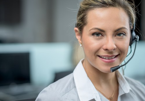 A female receptionist wearing a headset smiling at the camera