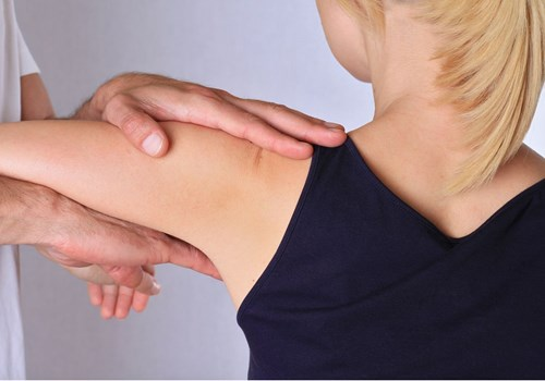 A male osteopath stretching a female patients shoulder