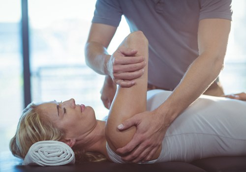 A male physiotherapist massaging a female patients shoulder while she lies on her back