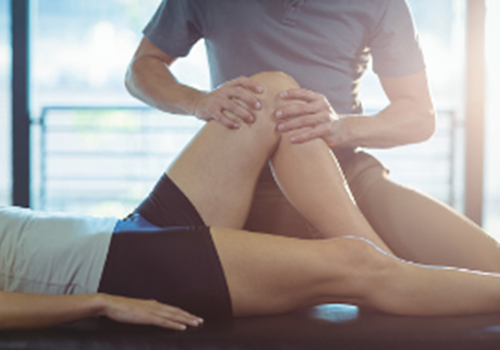 A male physiotherapist massaging a female patients knee while they lie on their back